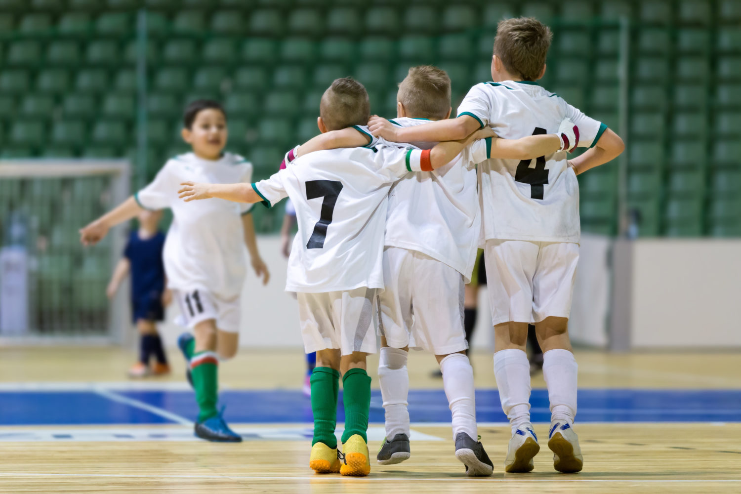 Indoor football soccer match for children. Happy kids together after winning futsal game. Chldren celebrate sport victory. Youth sport triumph