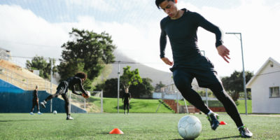 Football,Player,Training,In,Soccer,Field.,Young,Soccer,Player,Practicing